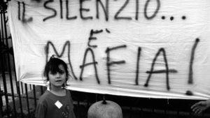 """Palermo , September 1993 - Demo against the killing of Father Puglisi - A female child in front of a banner with the writing """" Silence is Mafia """" Palermo , settembre 1993 - Protesta contro la mafia per l'uccisione di Padre Pugliesi - Una bambina di fronte ad uno striscione con la scritta """" Il silenzio  mafia """" *** Local Caption *** 00127716"""